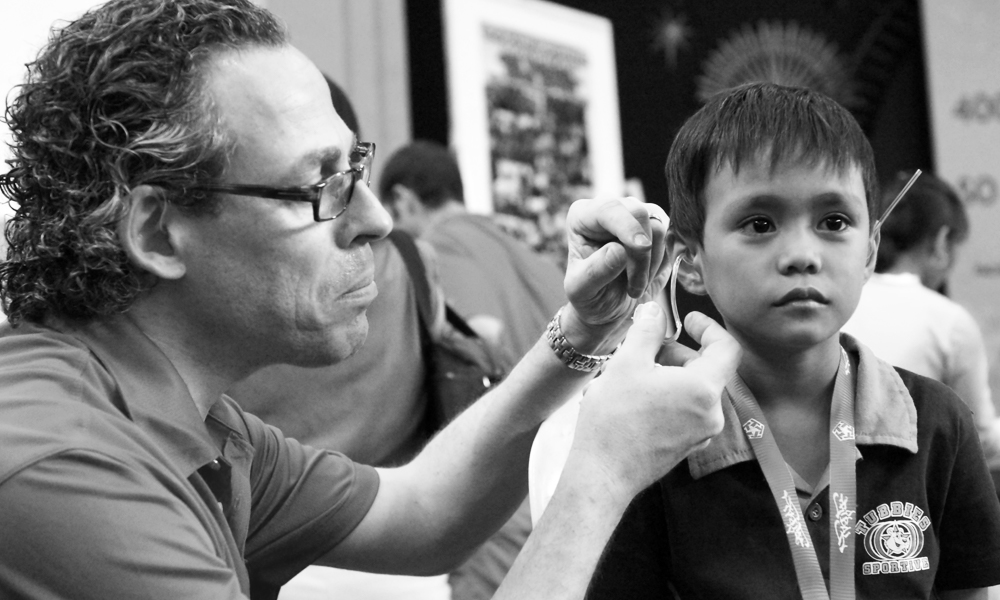 Bill Schiffmiller fitting a hearing ad on a Filipino child in need.