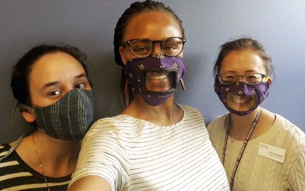 Young volunteers in clear-windowed face masks