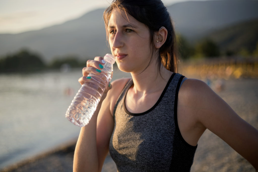 Young female drinking from a water bottle near body of water wearing a hearing aid