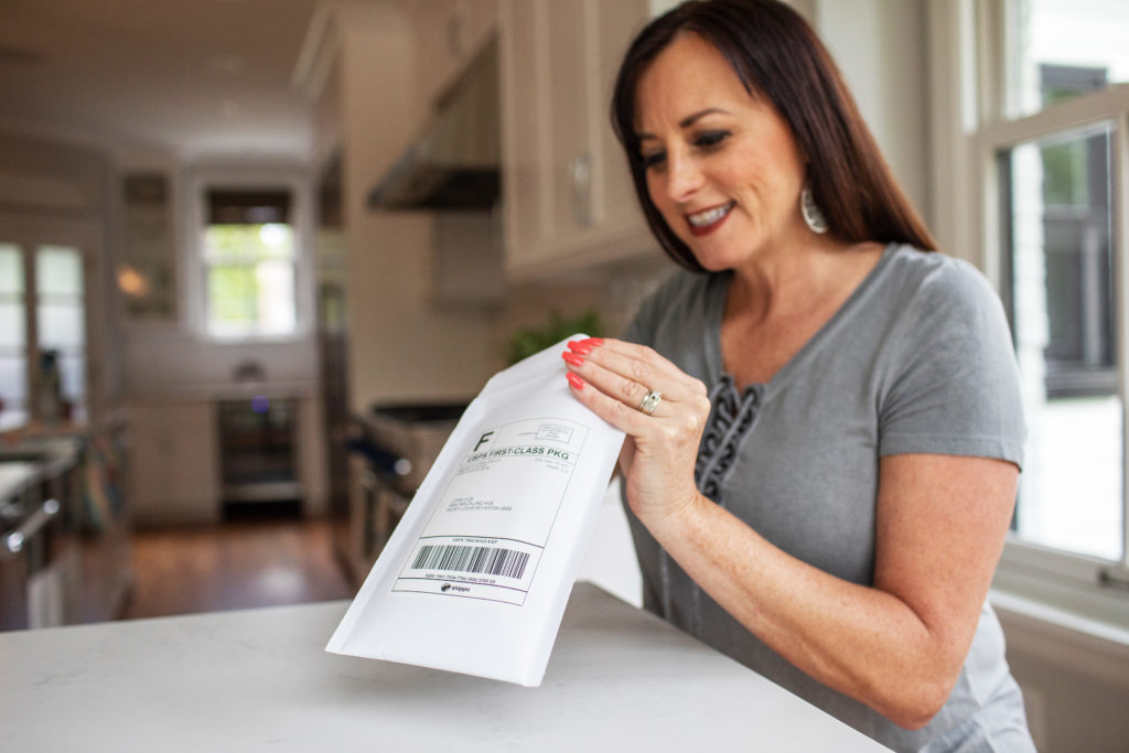 Smiling female with dark brown hair opening white envelope containing hearing aid batteries.