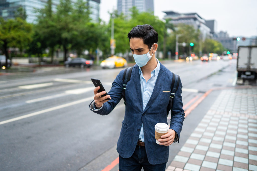 Man wearing a mask using a hearing aid and phone holding a cup of coffee in a city