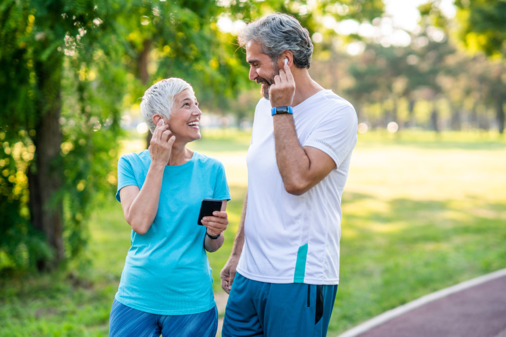 Two middle aged grey haired people sharing earbuds walking on a path for exercise